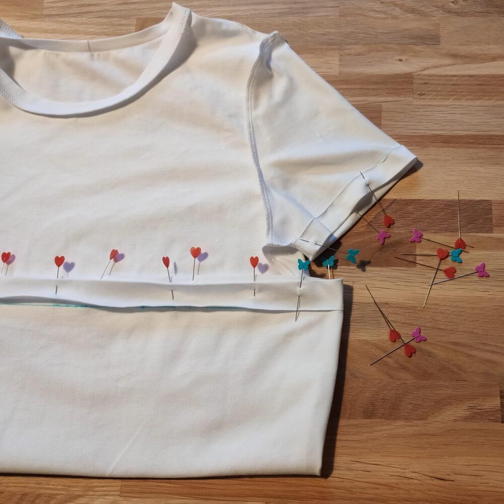 Saum und Ärmelsaum des T-Shirts stecken
