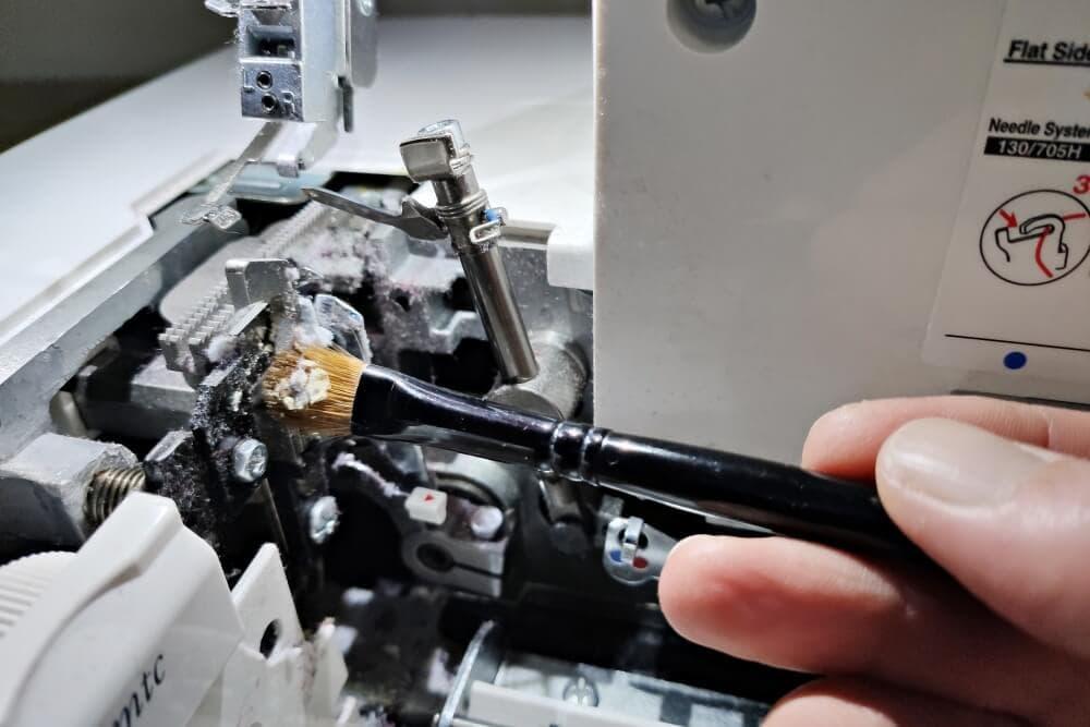 Nähstaub und Fadenreste bei einer Overlock mit einem Pinsel entfernen