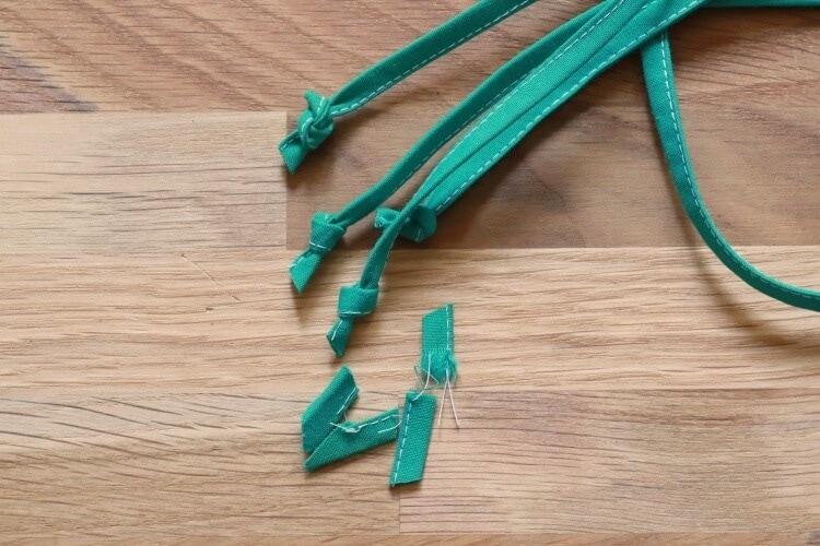 Bänder der Maske zum Binden verknoten